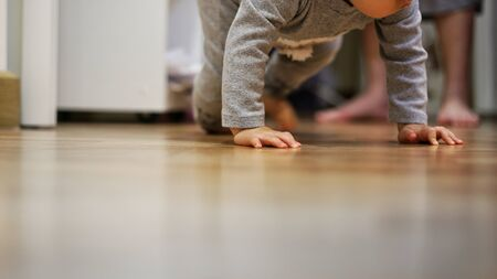toddler crawling on clean bedroom wooden floor while mother watching in the back. child development and baby growing up. Reklamní fotografie