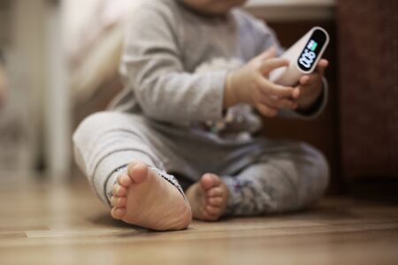 small baby children sitting on bedroom wood floor while holding a air quality sensor. baby learning and child development concept. focused on babys foot. growing up in pollution infested environment