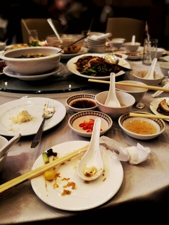 leftover food on a table after a big party. wasteful spending and lifestyle. food waste contribution to global warming problem situation. leftover Chinese food on round table. Reklamní fotografie
