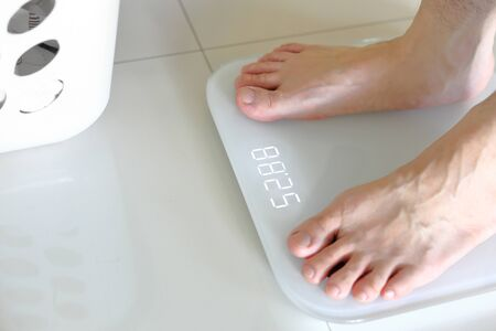 Bare feet standing on a scales. Lose weight concept with person on a scale measuring kilograms. Weight Scale, Underweight man on Scale. Stock Photo