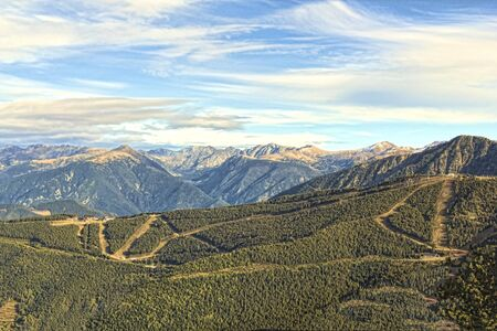 ski runs: Ski runs winding their way through the pines and views of the mountains beyond Stock Photo