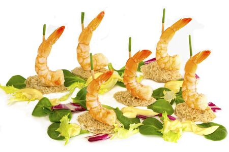 rapunzel: Crisp bread shapes and wooden sticks capped with onion stalks hold the shrimps upright  Lettuce, corn salad and red cabbage make up the sea  Stock Photo