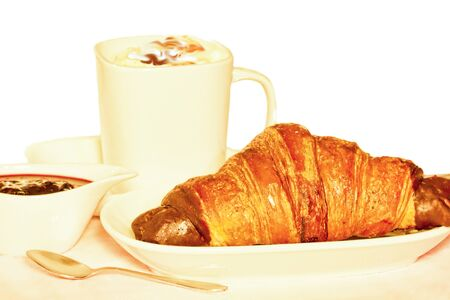 Cup of Creamy Caramel Coffee with a Chocolate Filled Croissant and a Dish of Plum Jam Stock fotó