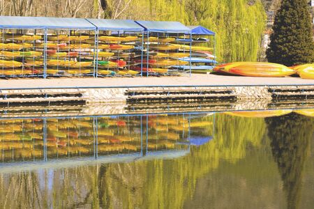 stillness: Many Coloured Canoes Stacked up in the Sports Boat Yard with Reflections in the Lake Water