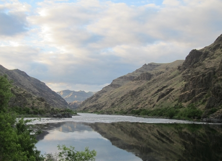 River reflects the canyon walls, mountains and beautiful sky
