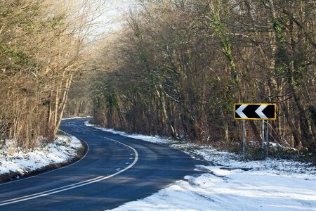 Countryside road and bends with left-pointing Road Bend Direction Sign photo