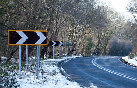 Countryside road and bends with right-pointing Road Bend Direction Sign photo