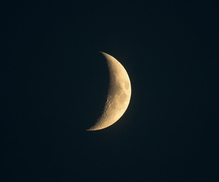 craters: Crescent moon with craters visible in sky not quite black