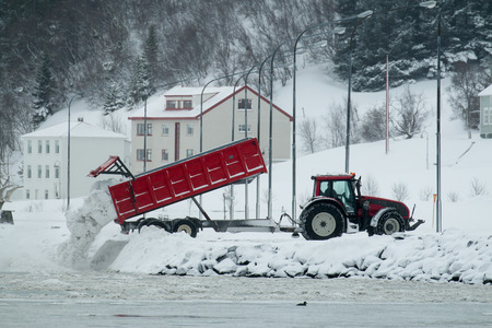 cleared: Tipper truck dumping cleared snow into Eyjafjordur fjord in Akureyri, Iceland. Stock Photo