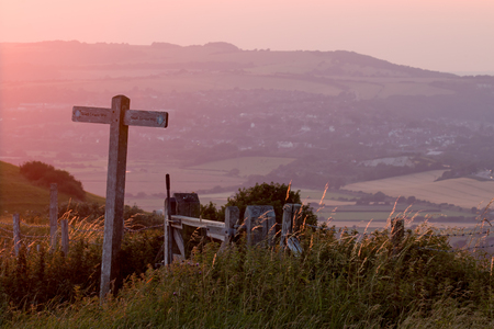 View from South Downs Way marker post near Firle Beacon across to Swanborough Hill in the west, at sunset.