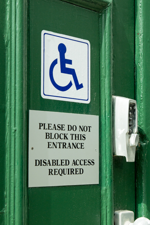 requirement: Door sign informing of requirement to leave access for disabled users. Stock Photo