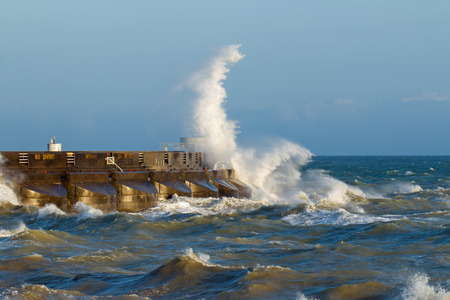 Waves breaking over the east arm of Brighton Marina, on the South Coast of England, during windy weather and high seas in the English Channel.