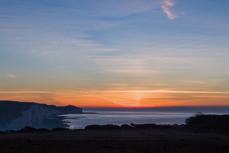 december sunrise: December sunrise from Seaford Head, looking South East over the English Channel with Belle Tout Lighthouse visible in the distance on the cliff-top. Stock Photo