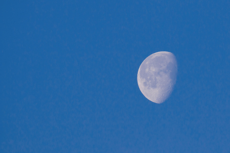 Waxing Gibbous Moon in blue sky showing craters, with copy space for text.