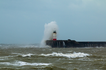 Newhaven Lighthouse in East Sussex, being battered by strong winds and crashing waves.