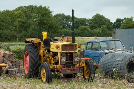 Old, rusting, yellow tractor on waste ground.