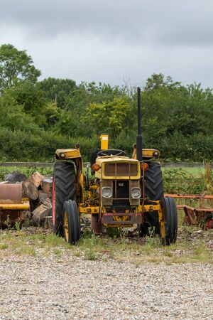 Old yellow tractor on waste ground.