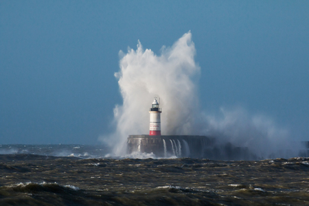 Breaking wave over Newhaven Lighthouse in East Sussex and rough sea.