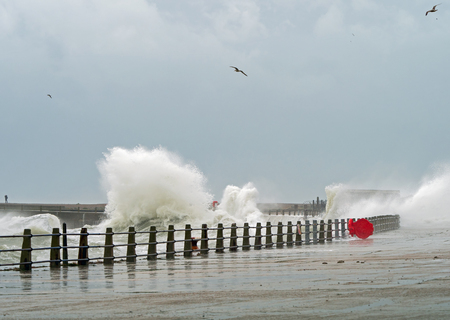 Waves Breaking at Newhaven Harbour with red lifebelt case.