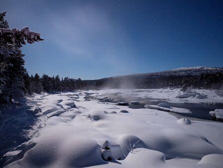 Moonlight over snowy scene by Juutuanjoki River in Finland. 版權商用圖片