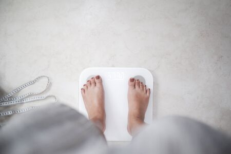 Cropped image of woman feet standing on weigh scales, A tape measure and dumbbell in the foreground.
