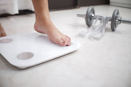 Cropped image of woman feet standing on weigh scales, A tape measure and dumbbell in the foreground