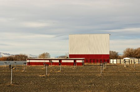 winter theater: Drive-in theater with a bright white and red screen, dirt parking area, and speakers on posts just waiting for warmer weather Stock Photo