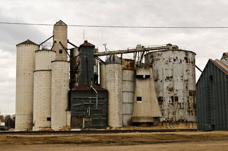 Grain elevators along railroad tracks in a small midwestern town in the US