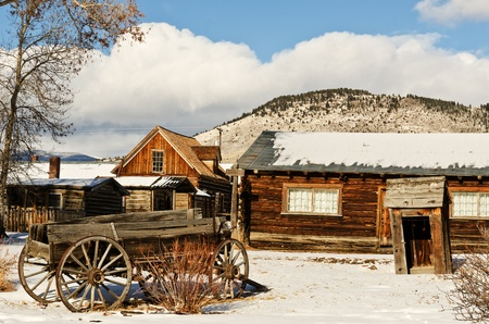 Old wagon sits among buildings in a Montana ghost town in the winter