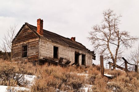 crumbling: Abandoned house on a hill with crumbling chimneys in winter Stock Photo