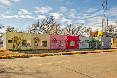 Brightly colored abandoned motel on the main street of a small town Stock Photo