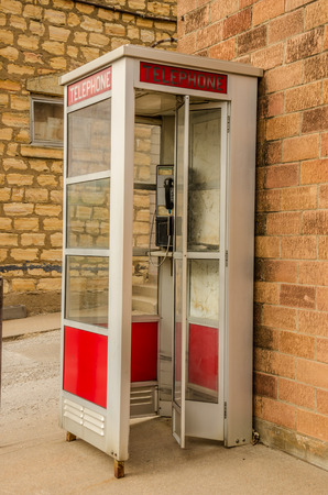 Red and white public telephone booth with a push button phone. Stock Photo