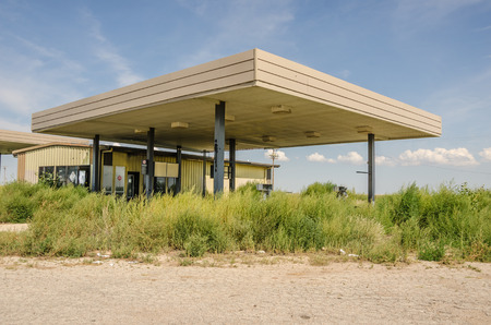 abandoned gas station: Abandoned service station on Route 66 with gas pumps destroyed and buried in the overgrown weeds Stock Photo