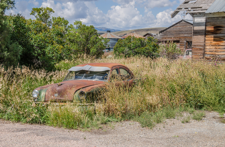 Rusty, old, abandoned automobile in an overgrown yard near silos, outbuildings, and an old truck on a beautiful summer day.