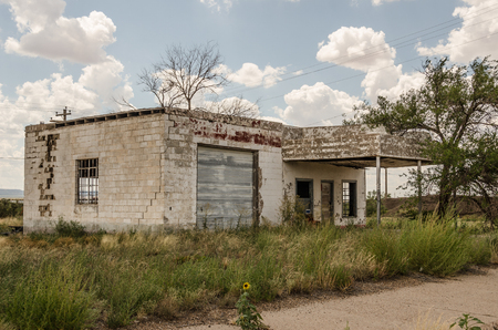 abandoned gas station: Neglected and abandoned former gas station and repair shop with a large crack in the building and lots of weeds in the yard on Route 66