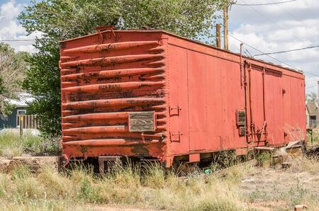 wood railroad: Railroad boxcar with a bit of rust  parked behind some homes.  Notice the three wood steps for help getting in.