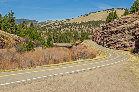 Winding road with  beautiful scenery and a 30 mph curve coming up on a Montana frontage road in spring