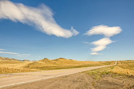 open road: Interesting clouds over an open road with no traffic in Big Sky Country Stock Photo