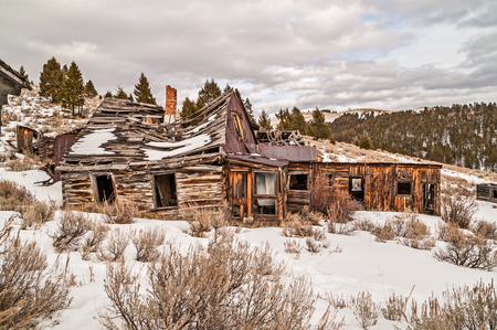 sagebrush: Abandoned home, business, or both with the main part falling down.  Notice the crooked brick chimney and a few other buildings nearby in similar conditions. Stock Photo