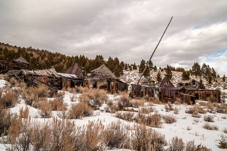sagebrush: Abandoned homes, businesses, and a flag pole on a winter day in a Montana ghost town