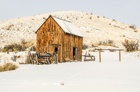 Dilapidated wagon, an outhouse, and a barn surrounded by fresh snow on a winter day