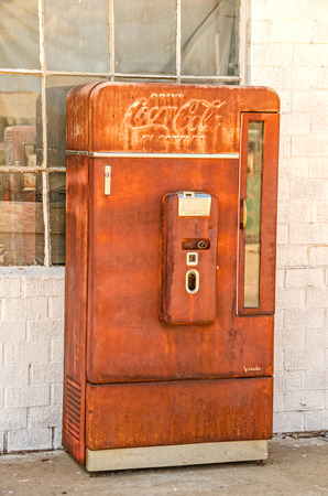 25 cents: ADRIAN, TEXAS - AUGUST 25, 2013:  Photo of an old, rusty Coca-Cola vending machine manufactured by Vendo and telling us to Drink Coca-Cola in Bottles at ten cents each