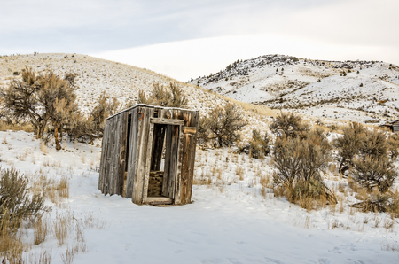 outhouse: Leaning outhouse with a rusty horseshoe hanging on the corner on a winter day Stock Photo