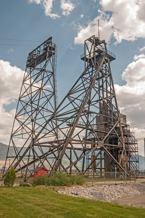 The historic Belmont Mine headframe with the Montana Resources open pit mine in the background. Dotting the landscape and skyline of Butte are fourteen tall, black steel structures.