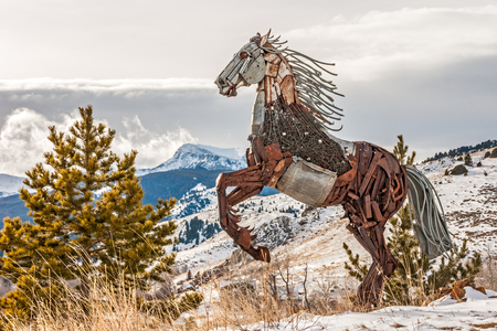 rearing: Rearing horse made of scrap metal standing on a hill overlooking a small town named Pony