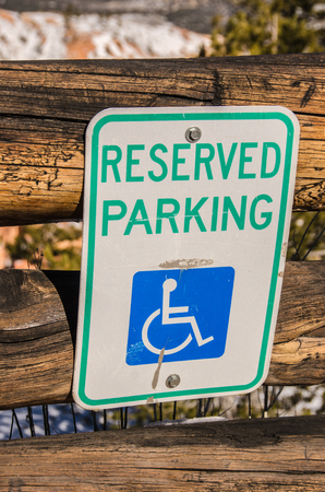 denoted: Reserved parking sign for handicapped people denoted by the wheelchair on the sign