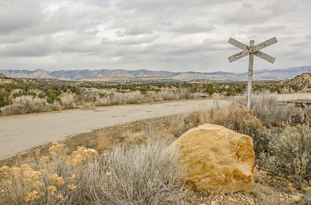 Old railroad crossing sign on a poorly maintained road in a rural area of Utah Stock Photo