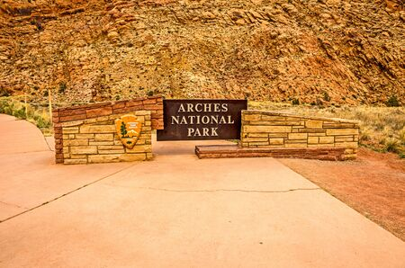 The sign at the entrance to Arches National Park in Utah blends beautifully with the background scenery. Stock Photo