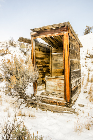 Alone in the snow stands this outhouse.  The door is missing and the structure is in an arrested state of decay.