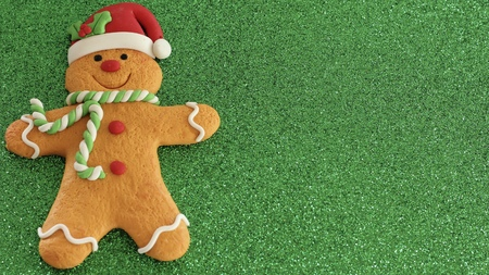 gingerbread man with Santa hat decorated laying flat on a green background Stock Photo